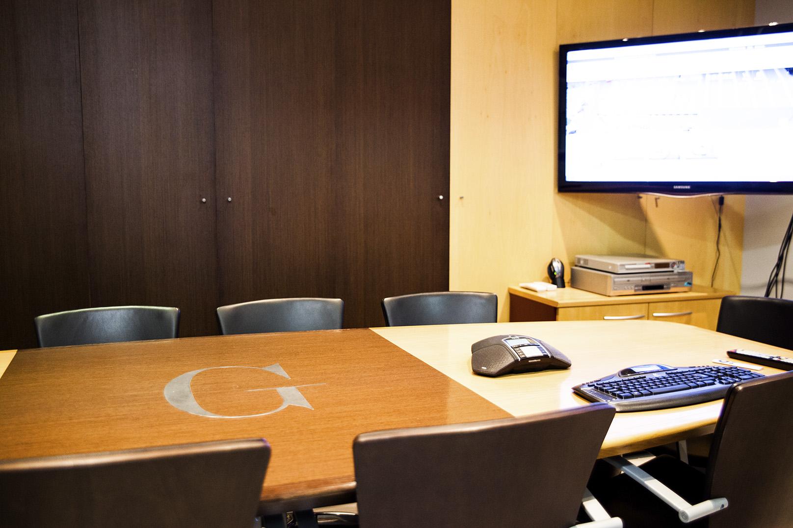 Sala de juntas con mesa y pantalla de televisión incorporada